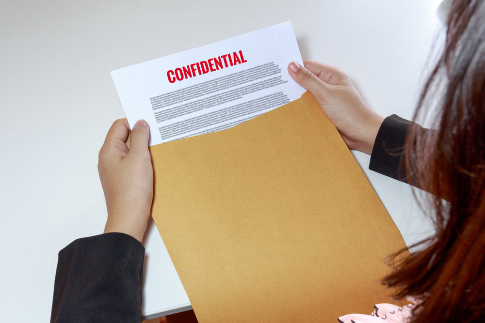 woman's hands holding a envelope with confidential paper