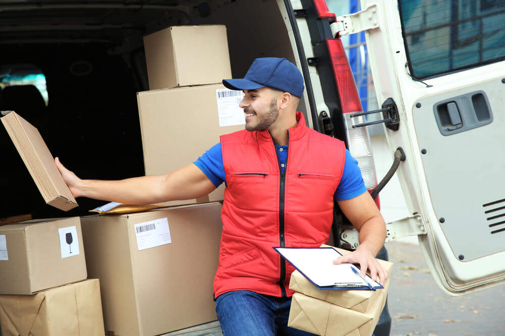 delivery driver wearing red vest in the back of delivery van with boxes in them